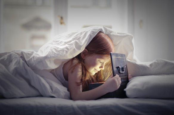 girl-lying-on-bed-looking-at-an-open-lighted-box-3887696